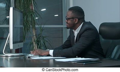 Successful african american businessman sitting at desk, working on generic laptop, typing a message
