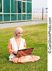 Successful Arab woman and laptop. Arab businesswoman wearing hijab working on a laptop in the park.