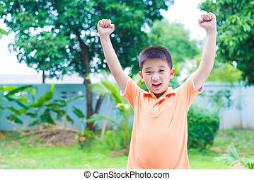 Successful Asian boy punching the air with his fists in air, smiling and shouting, in garden