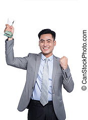 Successful asian businessman holding a trophy on white background