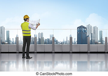 Successful asian engineer man with blueprint plan draft in ...