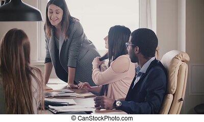 Successful attractive businesswoman encourages multiethnic...