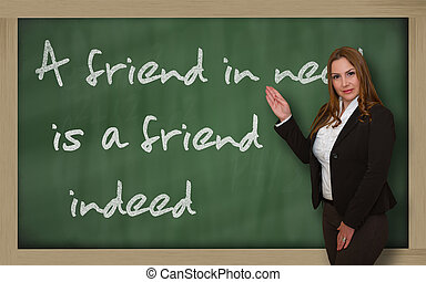 Successful, beautiful and confident woman showing A friend in need is a friend indeed on blackboard
