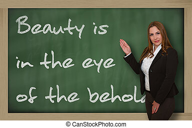 Successful, beautiful and confident woman showing Beauty is in the eye of the beholder on blackboard