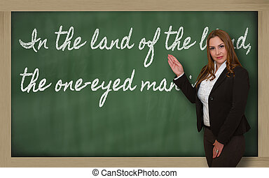 Successful, beautiful and confident woman showing In the land of the blind, the one-eyed man is king on blackboard