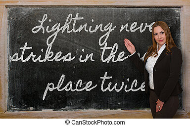 Successful, beautiful and confident woman showing Lightning never strikes in the same place twice on blackboard