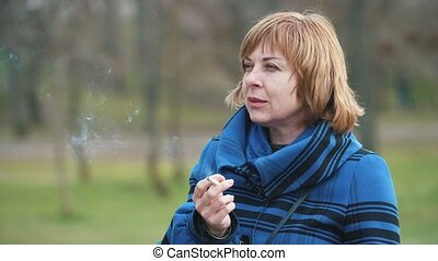 Successful blonde woman standing and smoking a cigarette in...