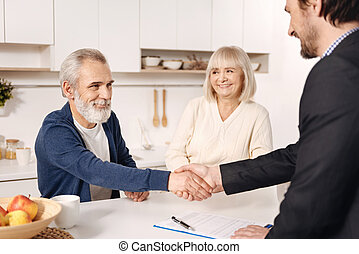 Successful broker meeting with elderly couple of clients