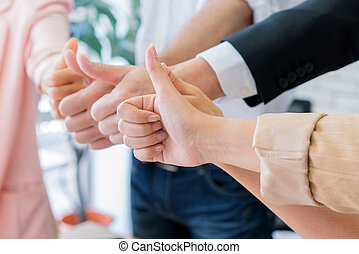 Successful business group with thumbs up in modern office