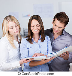 Successful business partners consulting a file together held...