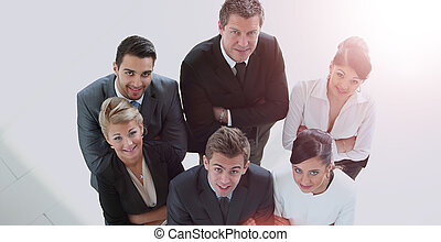 Successful business people looking up and smiling at office
