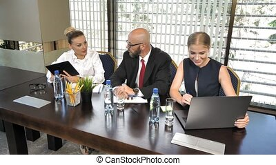 Successful business people with laptops in the conference room at a meeting in slow motion
