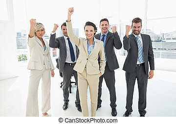 Successful business team clenching fists in office