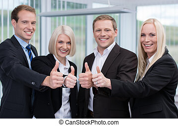 Successful business team giving a thumbs up