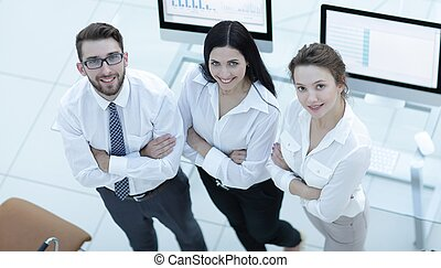 successful business team standing near workplace and looking...