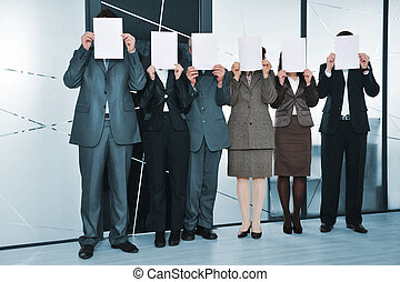 Successful business team standing holding white papers