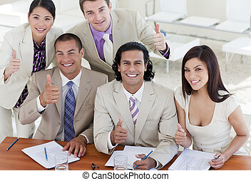 Successful business team with thumbs up in a meeting