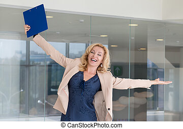 Successful business woman celebrating with arms up