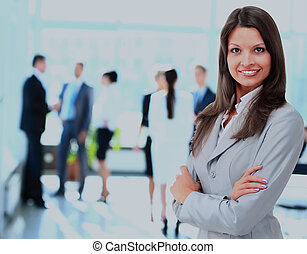 Successful business woman standing with her staff in background at office.