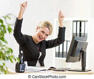 Successful business woman with arms up in office