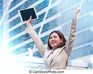 Successful business woman with arms up, outside corporate office.
