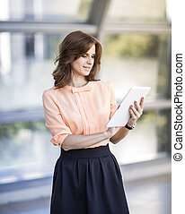 successful business woman with digital tablet standing in...