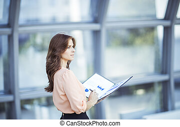 successful business woman with financial documents standing near a large window in a modern office