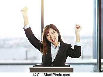 Successful business woman with hands up in office