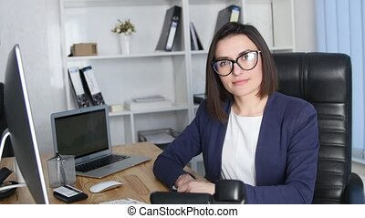 Successful business woman working at the office looking at camera and smile