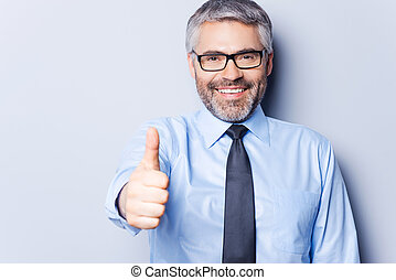 Successful businessman. Cheerful mature man in shirt and tie looking at camera and showing his thumb up while standing against grey background