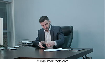 Successful businessman counting his money sitting in office