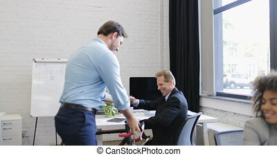 Successful Businessman Greeting With Coworkers Holding...