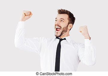 Successful businessman. Happy young man in shirt and tie gesturing while standing against grey background