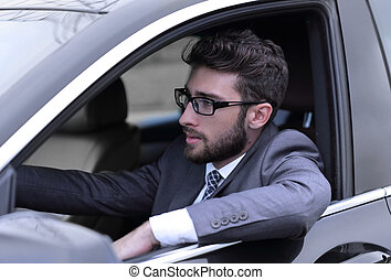 businessman in suit driving his luxurious car.