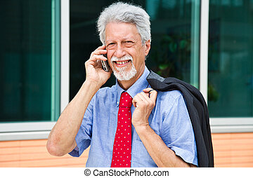 successful businessman is speaking on his smartphone