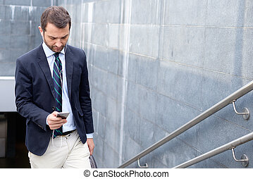 Successful businessman looking on his smartphone in the city street