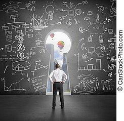 Successful businessman looking through key hole