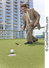 Successful Businessman Playing Golf on Skyscraper Rooftop - ...