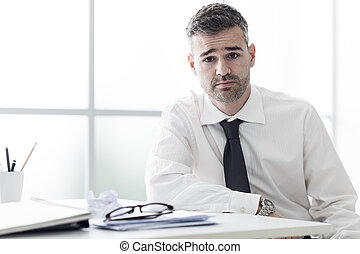 Successful businessman posing at his desk