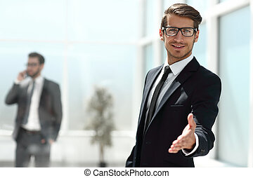 successful businessman reaching out for a handshake