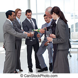 Successful businessman serving Champagne to his colleagues ...