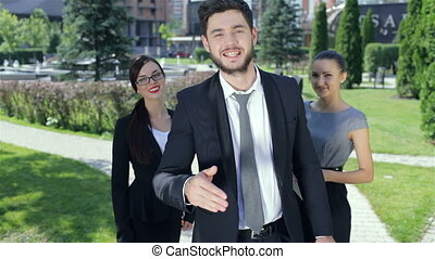 Successful businessman shaking hands standing in the company of two women
