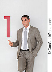 Successful businessman showing number one painted on wall