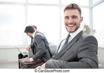 successful businessman sitting in an office waiting room