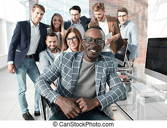 successful businessman sitting in front of business team