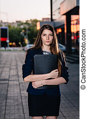 Successful businessman, standing against the backdrop of buildings holding  folder with sales charts. City business woman working.