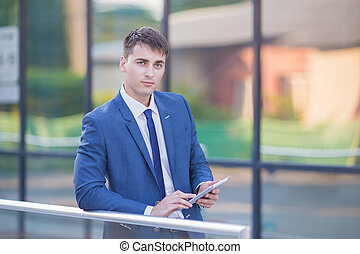 Successful businessman standing in the street holding a laptop