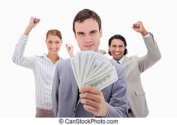 Successful businessman with cheering colleagues against a...