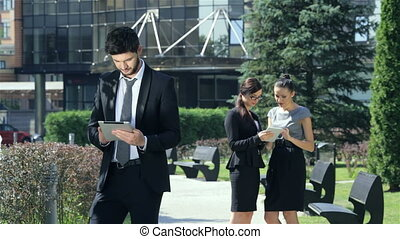 Successful businessman with tablet stands on the background of two businesswomen