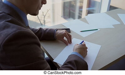Successful businessman writes on sheet, sitting at table in...